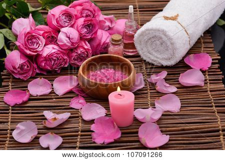 Rose with rose petals, salt in wooden bowl ,candle on mats