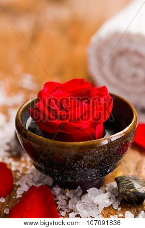 Rose in bowl with pile of salt ,stones on old wooden board