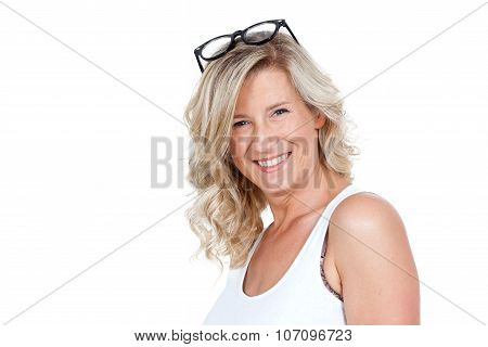 Beautiful adult woman, blonde, smiling, beautiful face. He has glasses on her head. Strong mature