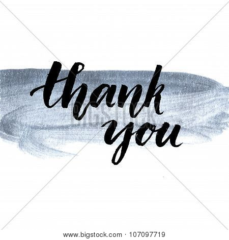 Thank you. Calligraphy phrase handwritten on silver paint stroke. Brush lettering for client service