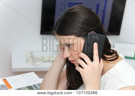 Attractive Business Woman Use Smart Phone And Sitting At Her Worktable With Documents And Electronic