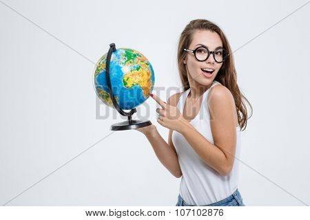 Portrait of a cheerful woman pointing finger on globe and looking at camera isolated on a white background