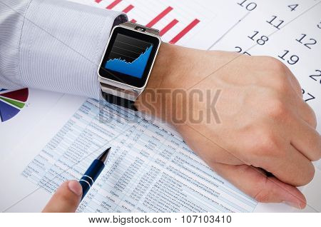 Man Working With Smart Watch In Office