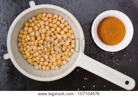 Boiled chickpeas in a colander and spices on black metal background