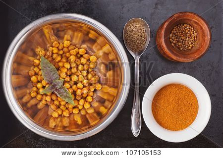 Baked spiced chickpeas in metal bowl, paprika, cumin seeds and coriander seeds on black surface