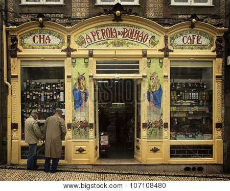 PORTO-PORTUGAL NOVEMBER 4, 2015: Two old men looking a window in a little cafe and store in Porto, Portugal