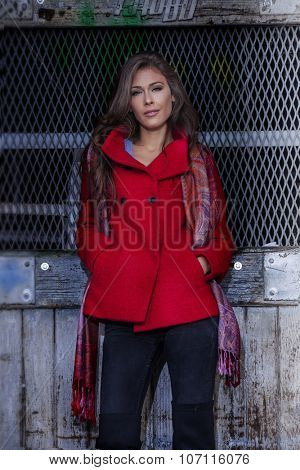 fashionable young woman  wearing red coat and cashmere scarf stand in front old grid door, outdoor in the city