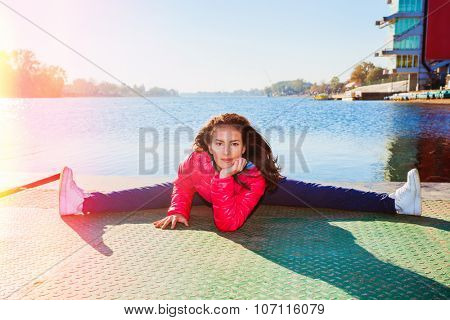 young woman in tracksuit and red jacket in splits position on  pontoon at lake,  sunny autumn day, full body shot