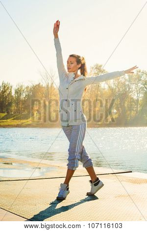 young woman in tracksuit exercise on pontoon at lake,  sunny autumn day, full body shot, stretching