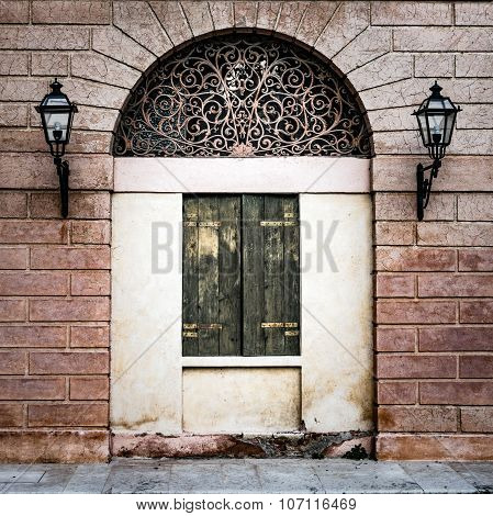 Facade Of An Ancient Italian Villa With Artistic Iron Grill.