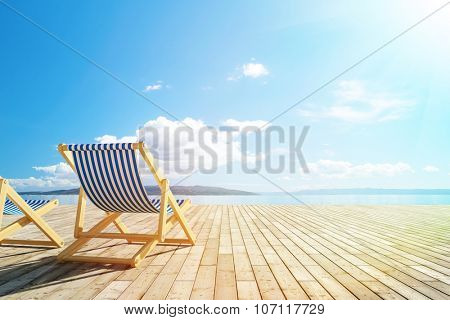 Pool deck with lounge chairs and view of sea