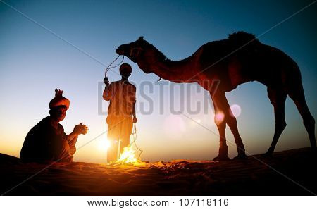 Two Indigenous Indian Men Resting Camel Concept