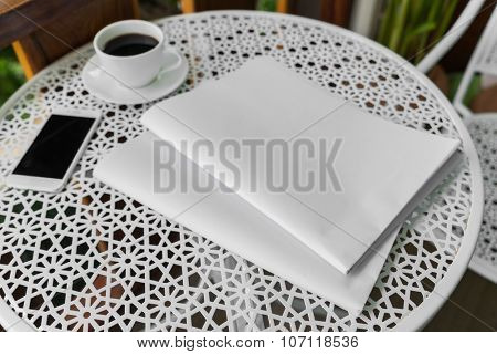Blank Newspaper with empty space and coffee cup ,mobile phone mock up on table