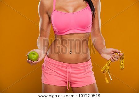 Young sport woman body measuring waist with tape measure and green apple emotions smiling on yellow