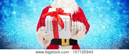 christmas, holidays and people concept - close up of santa claus with gift box over lights or blue glitter background