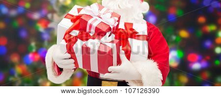 christmas, holidays and people concept - close up of santa claus with gift boxes over lights background