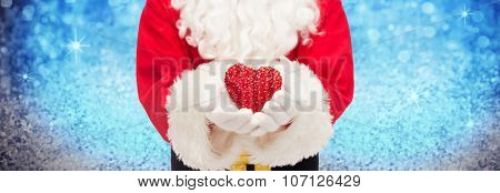 christmas, holidays, love, charity and people concept - close up of santa claus with heart shape decoration over lights or blue glitter background
