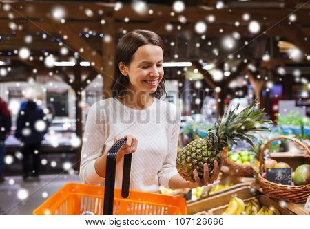 sale, shopping, consumerism and people concept - happy young woman with food basket in market or grocery store over snow effect