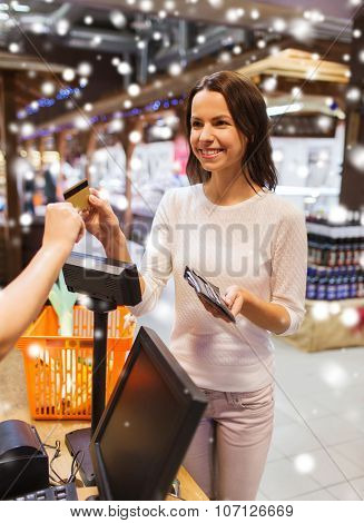 sale, shopping, consumerism and people concept - happy young woman with credit card and wallet buying food at checkout in market over snow effect