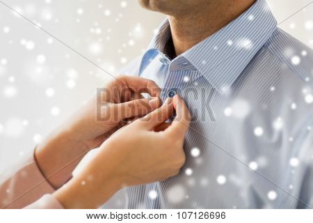people, business, care and clothing concept - close up of woman helping man and fastening button on his shirt at home over snow effect