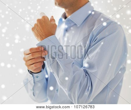 people, business, fashion and clothing concept - close up of man fastening buttons on shirt sleeve at home over snow effect