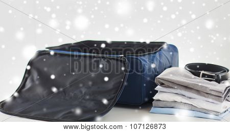 business trip, luggage and clothing concept - close up of travel bag, shirts, trousers and belt over snow effect