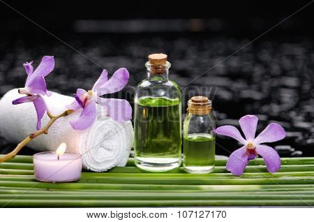 Set of orchid with candle ,towel ,oil on long plant â??wet background