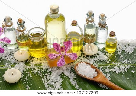 Spa set on banana leaf with pile of salt, yellow orchid