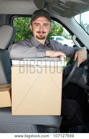Young delivery man in the car. Parcel service.