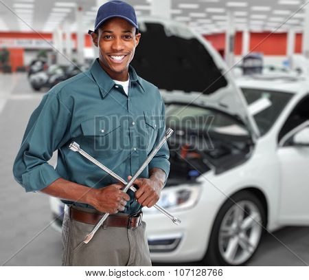 Smiling car mechanic with wrench in auto repair service.