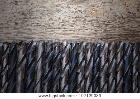 Old Rusty Drill Bits On Wooden Table