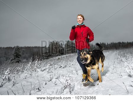 Young lady running in snowy winter field with the dog