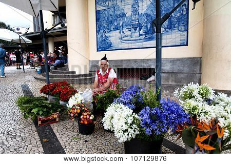 Funchal, Portugal - June 29, 2015: A Traditional Woman Sells Flowers At The Famous Mercado Dos Lavra