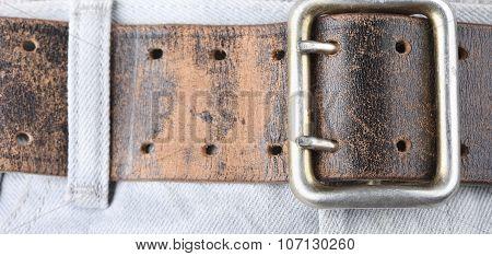 Old vintage leather belt jeans closeup