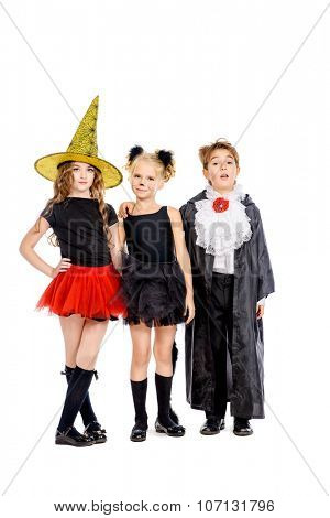 Group of cute children wearing halloween costumes posing over white background. Halloween concept. Isolated over white.
