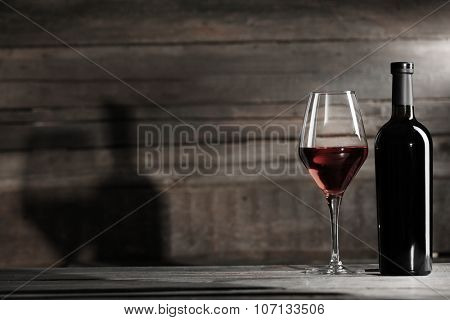 Wine bottle with glass on wooden background,  black and white retro stylization
