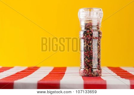 Colored Peppers Mix And Pepper Mill On Tablecloth