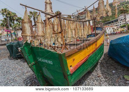 CAMARA DE LOBOS, PORTUGAL - JULY 23, 2015: View of fishing boat and dry fish hanging in Camara de Lobos town in south of Madeira island, Portugal
