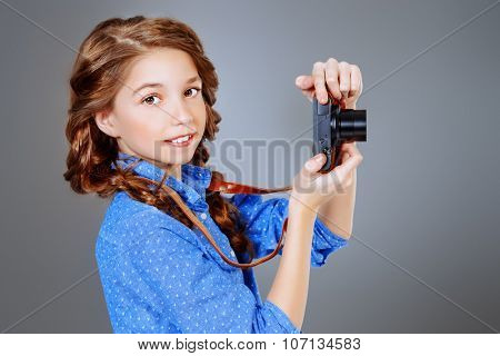 Cute smiling girl photographing on camera. Studio shot.