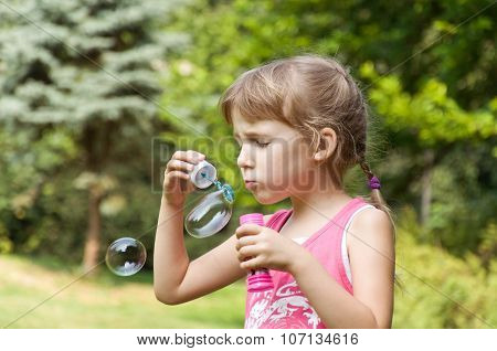 Little Girl In The Park Inflates Soap Bubbles