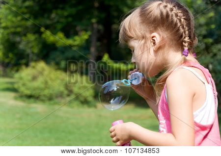 Girl In The Park Inflates Soap Bubbles
