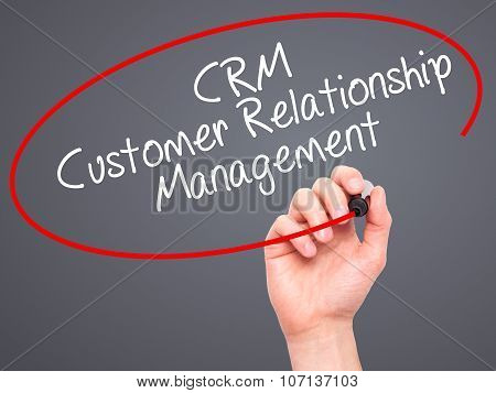 Man Hand writing CRM Customer Relationship Management with black marker on visual screen.