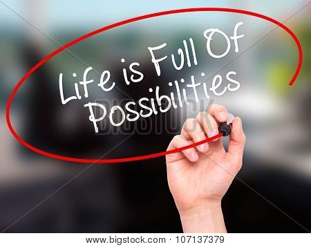 Man Hand writing Life is Full Of Possibilities with black marker on visual screen.