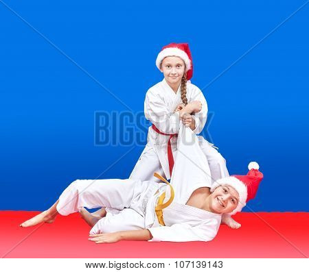 Children in cap of Santa Claus are training throws