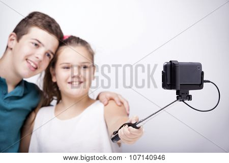Brothers taking a picture with a selfie stick on grey background