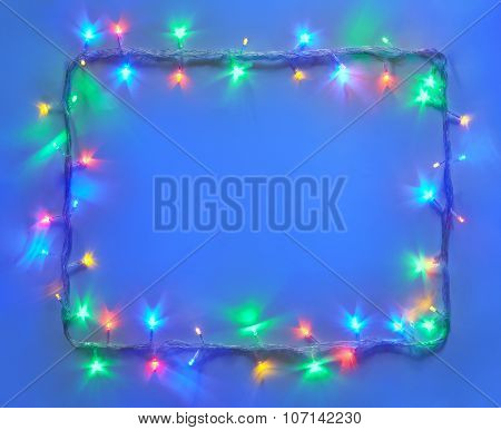 Christmas Lights Frame On Blue Background With Copy Space.
