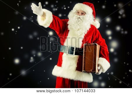 Santa Claus stands with suitcase and shows the direction, black background. Christmas time.