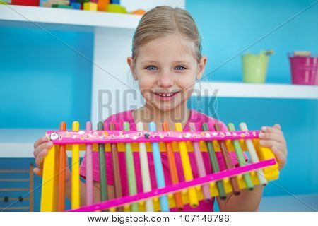 Smiling girl holding a xylophone in her room