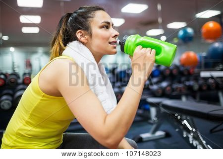 Woman taking a drink from her water bottle at the gym