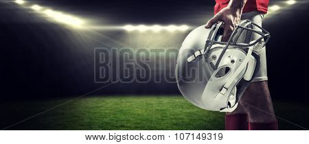 American football player holding helmet against rugby stadium